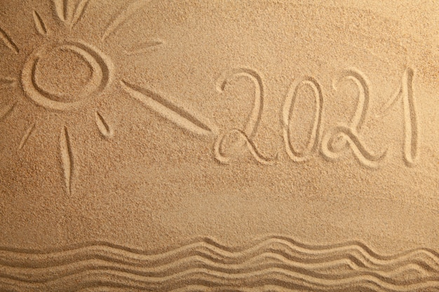 2021 new year text with sun on sand background Premium Photo