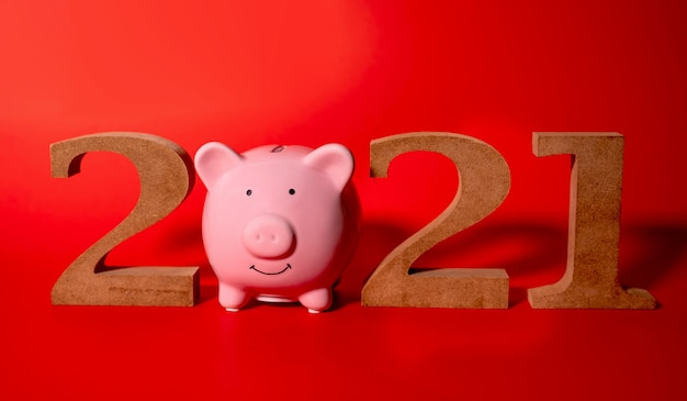 2021 wooden character and pink piggy bank on white background, concept holidays christmas new year. Premium Photo