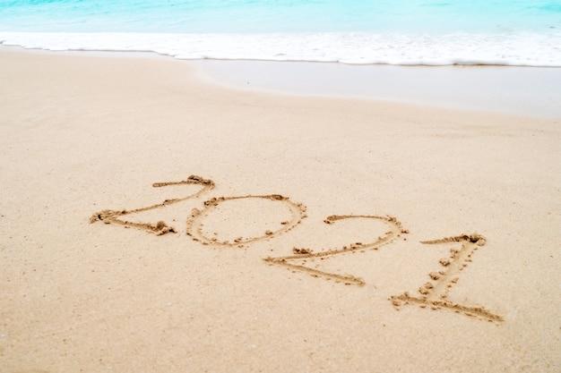 Premium Photo   2021 year hand drawn on sand summer beach.