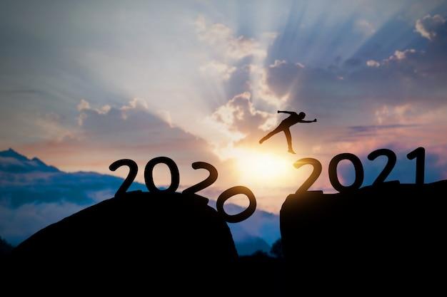 2021成功シルエットコンセプト、男が山の上に新年にジャンプ Premium写真