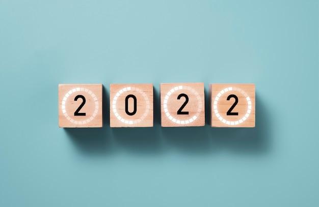 파란색 배경, 메리 크리스마스와 새 해 복 많이 받으세요 준비 개념 나무 큐브 블록에 기호를로드와 함께 2022 년. 프리미엄 사진