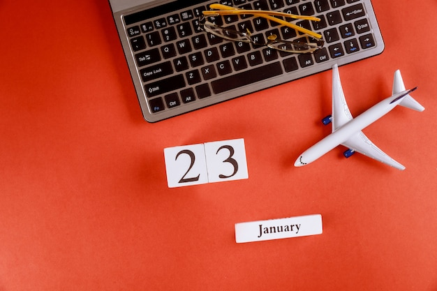 23 january calendar with accessories on business workspace office desk on computer keyboard, airplane, glasses red background Premium Photo