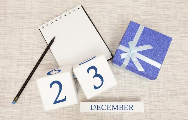 Кубический календарь на 23 декабря и подарочная коробка, рядом блокнот с карандашом Premium Фотографии
