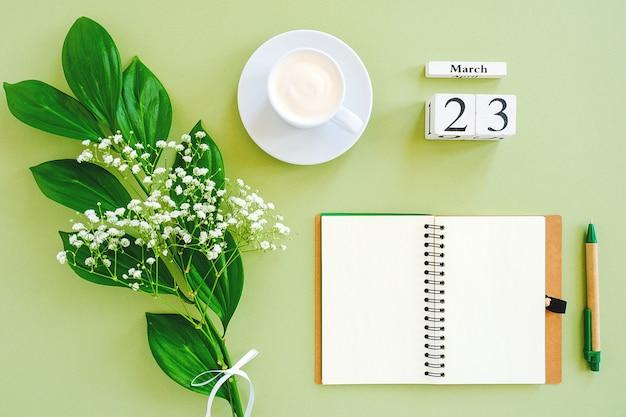 Календарь 23 марта. блокнот, чашка кофе, букет цветов на зеленом фоне. Premium Фотографии