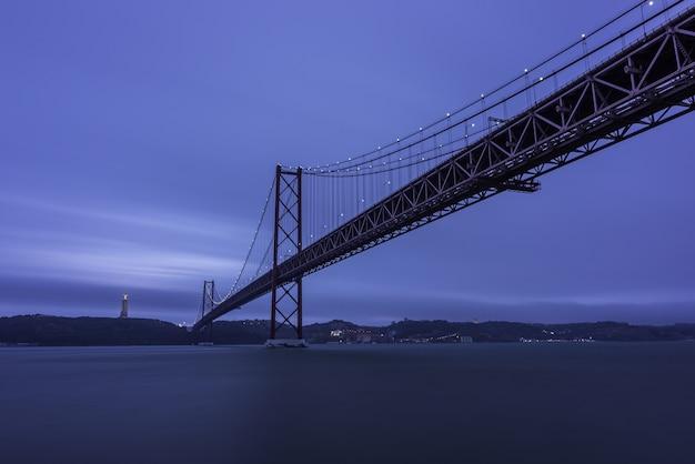 夕方には丘と光に囲まれたテージョ川に架かる25de abril bridge 無料写真