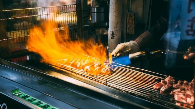 従業員は、台湾の台北で販売される肉を焼きます-2562年6月11日 Premium写真