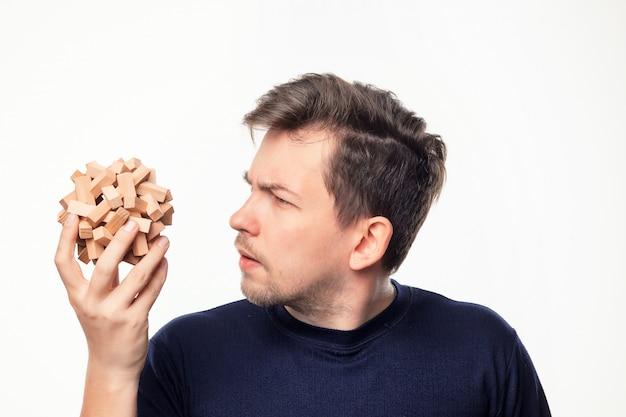Привлекательный 25-летний деловой человек, глядя путать на деревянные головоломки. Бесплатные Фотографии