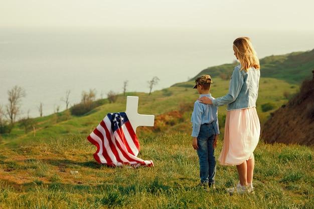 お母さんと息子は記念日27日に父親の墓を訪れました Premium写真