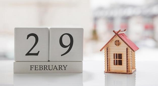 Февральский календарь и игрушечный дом. 29 день месяца сообщение карты для печати или запоминания Premium Фотографии