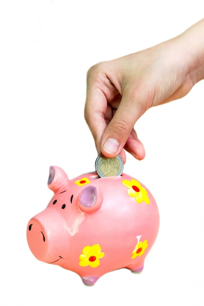 女の子はピンクの貯金箱にコイン2ユーロを入れます。 Premium写真