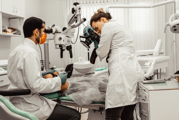 2人の歯科医が患者を治療します。プロのユニフォームと歯科医の機器。ヘルスケア医師の職場を装備します。歯科 Premium写真