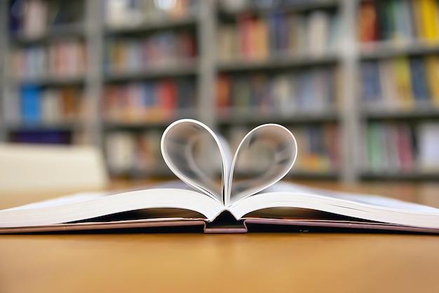 読むライフスタイルのライブラリと2月のバレンタインの日の概念のライブラリでテーブルの上のハート形の本のイメージを閉じます。 Premium写真