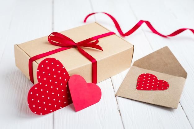 赤いリボン、2つの赤いハート、白い木製の背景にラブレターとギフトボックス Premium写真