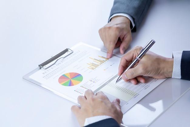 投資収益率に関する財務諸表レポートをレビューしている2人のビジネスマンまたはアナリスト Premium写真