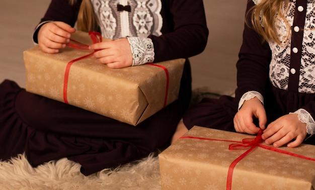 ブルゴーニュレースのレトロなドレスを着た2人の女の子がクリスマスプレゼントを開く Premium写真