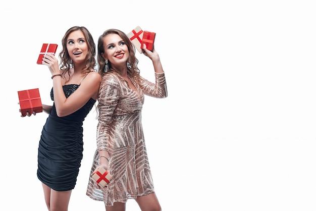 白で隔離の手の中に赤いプレゼントを持つ2人の若い女の子 Premium写真