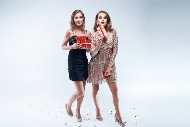 白で隔離の手の中に赤いプレゼントを2人の若い女性 Premium写真