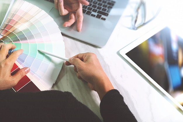 スマートフォンとデータとデジタルタブレットとコンピューターのラップトップを議論する2人の同僚のウェブデザイナー Premium写真
