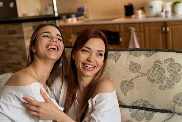 自宅のソファーに座っているブルージーンズの2つの若い美しい陽気なガールフレンドは笑っています。 Premium写真