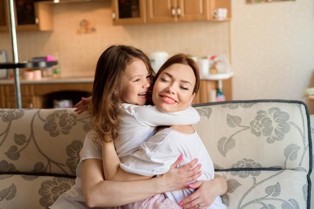 2人の姉妹と小さな娘笑顔とホームインテリアの背景で抱き締めます。 Premium写真