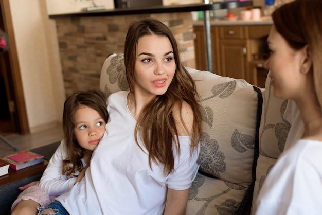 2人の姉妹とソファに座っている少女の肖像画 Premium写真