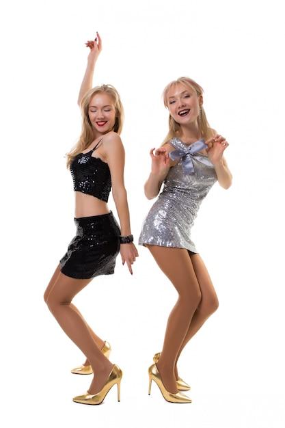 分離された光沢のあるドレスで白で踊る2つのかわいいヨーロッパの双子の女の子 Premium写真
