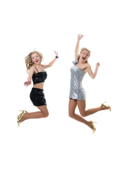 2人の美しい幸せな女の子が分離された白でジャンプしています。買い物の喜びフリーズジャンプ、女の子の飛行。 Premium写真