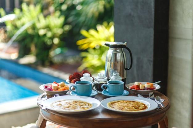 木製のテーブルにホットドリンクの2つの青いカップと伝統的なバリの朝食 Premium写真