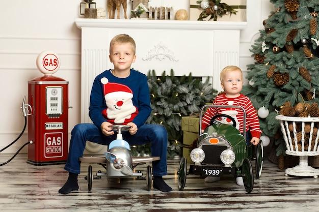 かわいい2人の弟がおもちゃの車で遊んでいます。幸せな子供時代。 Premium写真