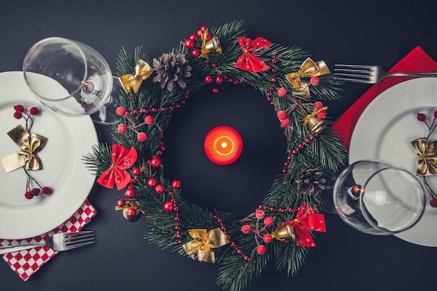 2つの美しいクリスマスディナーの場所の設定。花輪とキャンドルで飾られたテーブル。 Premium写真