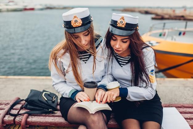 制服を着て海で本を読んで海洋アカデミーの2人の女子大生。勉強している友達 Premium写真