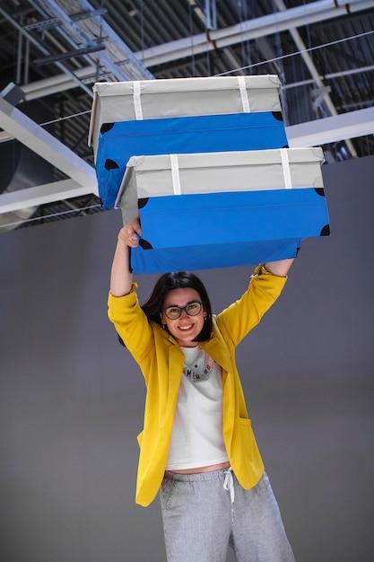 灰色の背景に2つの青いスーツケースを持つ陽気な女の子旅行者。 Premium写真