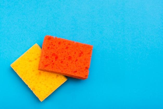 青色の背景に皿を洗うための2つのきれいな新しい色のスポンジ。掃除機のコンセプト。 Premium写真