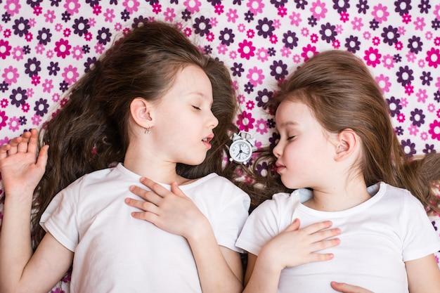 2人の眠っている少女とその間の白い目覚まし時計。上面図 Premium写真
