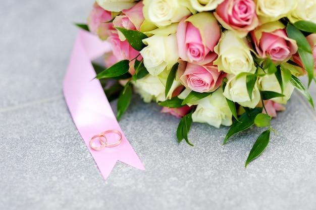 黄色とピンクのバラと2つの金の結婚指輪の美しい結婚式の花の花束 Premium写真