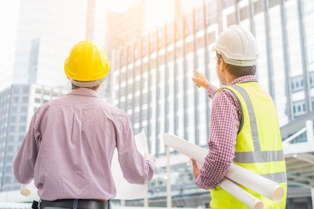 План азиатского инженерства 2 проверяя на строительной площадке. Premium Фотографии
