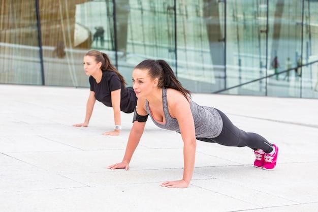 腕立て伏せ運動をしている2人の女性 Premium写真