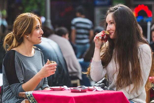 イスタンブールのケイ、伝統的なトルコの紅茶を飲む2人の女性 Premium写真