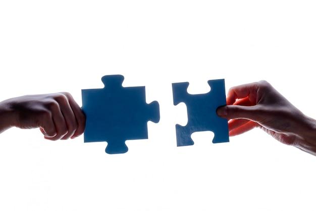 白地に青いジグソーパズルのピースのカップルを持っている2つの手のシルエット Premium写真
