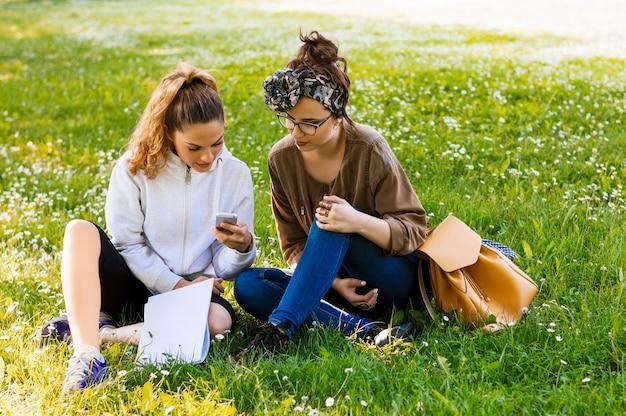 公園の芝生の上に座っている2人の女性 Premium写真