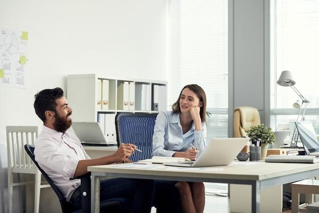 机に座ってチャットする2人の同僚のミディアムショット 無料写真