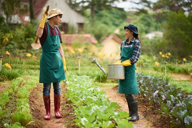 庭の真ん中でおしゃべりをしている2人の農家のフルショット 無料写真