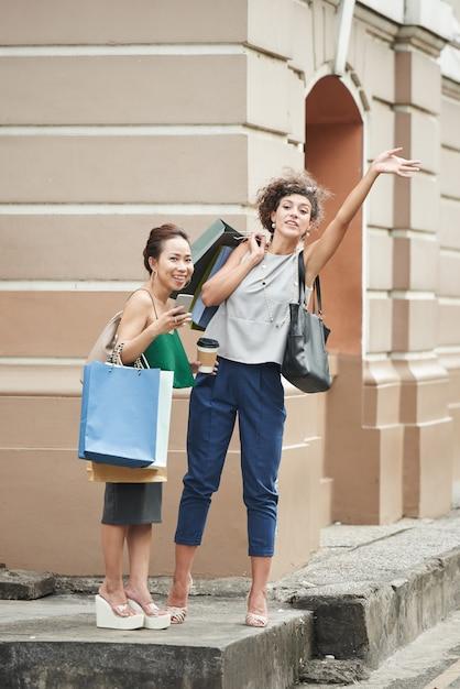 通りでタクシーを引く買い物袋を持つ2つの女性の友人 無料写真