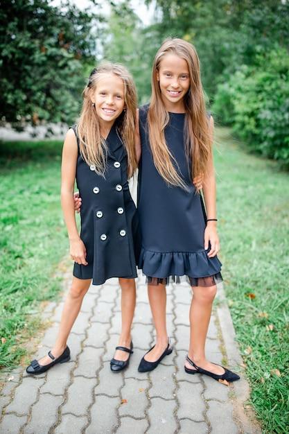 学校の前でポーズをとる2つのかわいい笑顔の女の子。 Premium写真