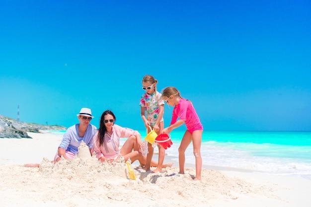 熱帯のビーチで砂の城を作る2人の子供連れのご家族 Premium写真