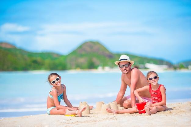 熱帯の白いビーチで砂の城を作る家族。父と熱帯のビーチで砂と遊ぶ2人の女の子 Premium写真