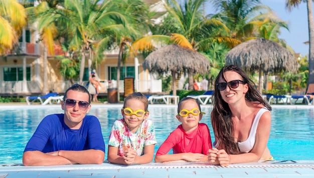 2人の子供を持つ若い家族は、屋外プールで夏休みを楽しむ Premium写真