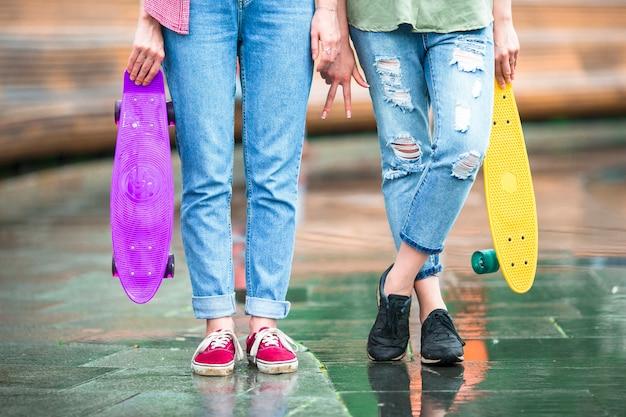 夕日の光の中で屋外スケートボードと2つの流行に敏感な都市の女の子 Premium写真