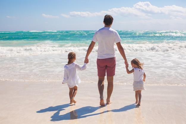 父と白い砂浜の上を歩く彼の2人のかわいい娘の背面図 Premium写真