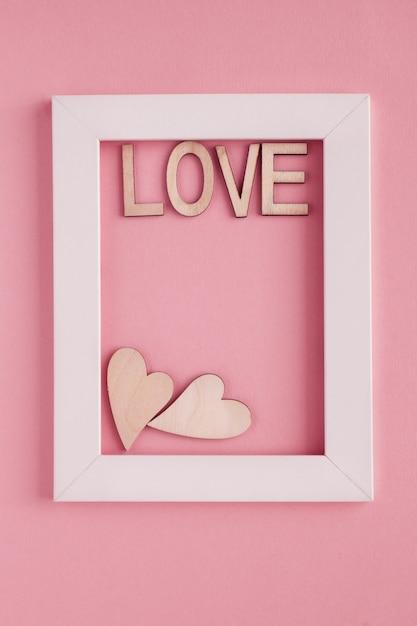 ピンクの背景に白いフレームで2つの心と木製の文字という言葉が大好き Premium写真